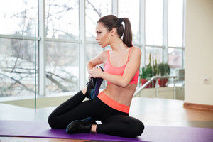 Attractive serious young sportswoman sitting on yoga mat and stretching legs in gym
