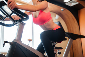 Attractive strong young woman athlete riding on bicycle in gym