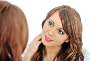 Attractive woman applying makeup while looking at the mirror