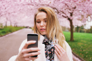Attractive woman photographing herself at the spring garden. Beautiful young female model taking self portrait with her mobile phone.
