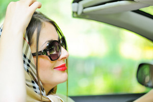 Attractive woman with headscarf sitting in driver seat in the car