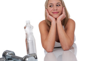 Attractive woman with weights and bottle of water on white background