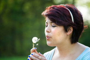 Attractive young brunette woman under soft natural lighting blowing on a dried dandelion. Shallow depth of field.