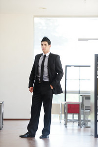 Attractive young businessman standing in office alone