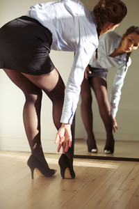 Attractive young businesswoman looking in to mirror while wearing high heels shoes. Caucasian female model getting dressed.