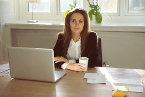 Attractive young businesswoman sitting at her desk with laptop looking at camera. Beautiful woman sitting at table in her home office. Caucasian woman portrait working from home.