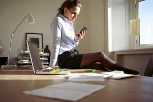 Attractive young businesswoman sitting on her desk in modern office looking at her smart phone. Female model in blue shirt and skirt using mobile phone in home office