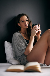 Attractive young female model drinking coffee while sitting in bed. Woman drinking coffee in morning in bedroom.