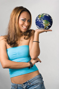 Attractive young hispanic woman holding the world in her hands.  Earth photo courtesy of NASA.