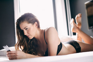 Attractive young lady lying on bed using her cell phone. Caucasian female in black lingerie in bedroom.