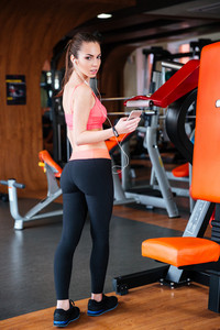 Attractive young sportswoman standing and listening to music from smartphone in gym