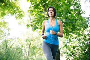 Attractive young sporty woman in headphones running outdoors in park