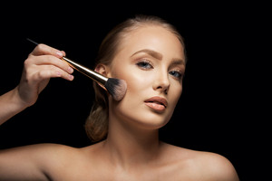 Attractive young woman applying foundation on her face with a make up brush against black background. Pretty young caucasian model.