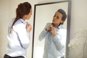 Attractive young woman in front of mirror buttoning up her shirt. Beautiful caucasian female getting dressed for office.