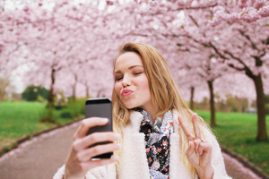 Attractive young woman posing for selfie. Beautiful female at spring blossom park taking self portrait with mobile phone.