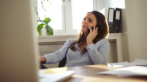 Attractive young woman sitting at her desk talking on mobile phone. Pretty caucasian businesswoman working in home office.