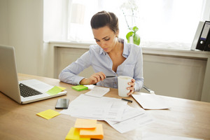 Attractive young woman working at the desk with sticky notes and laptop. Beautiful businesswoman reading notes while sitting in home office.