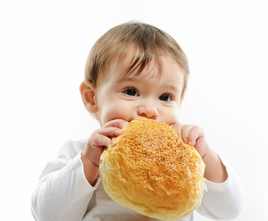 Baby eating bun bread