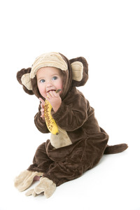Baby in monkey costume holding banana