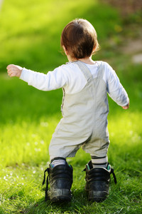 Baby kid walking on the green grass wearing big shoes