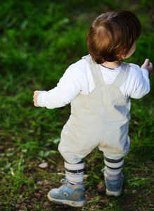 Baby kid walking on the green grass