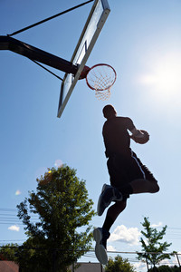 Back lit silhouette of a basketball player going up for a reverse jam.