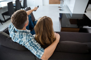 Back view of beautiful couple watching tv on sofa in living room