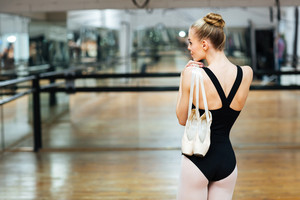 Back view portrait of a ballerina standing and holding pointe shoes in ballet class