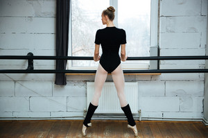 Back view portrait of a beautiful ballerina standing on poite in ballet class