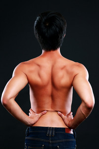 Back view portrait of a man stretching on black background