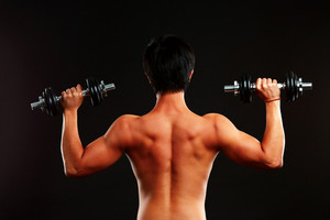 Back view portrait of a man working out wirh dumbbells