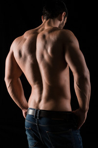 Back view portrait of a muscular man posing on black background