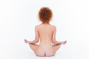 Back view portrait of a nude woman meditating isolated on a white background