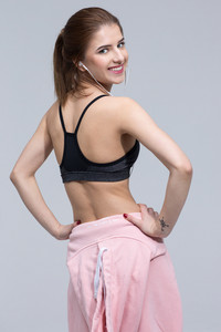 Back view portrait of a smiling sports woman over gray background