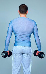 Back view portrait of a sport man standing with dumbbells on gray background