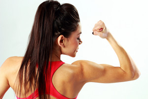 Back view portrait of a young sport woman looking at her biceps on gray background