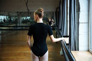 Back view portrait of a young woman practicing in ballet class