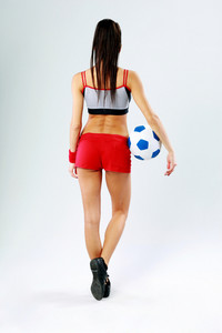 Back view portrait of a young woman standing with soccer ball on gray background
