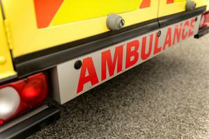 Backside view of yellow ambulance car sign