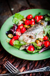 Baked Seabass With Tomatoes And Basil On Rustic Wooden Background