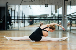 Ballerina doing stretching exercises on the floor in ballet class