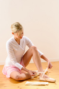 Ballerina getting dressed for ballet performance woman pointe tying dressing