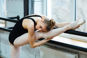 Ballerina resting leg in ballet class