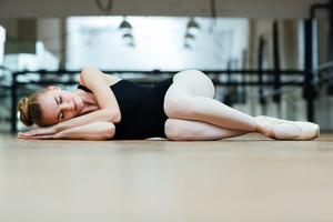 Ballerina sleeping on the floor in ballet class