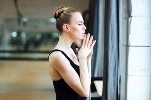 Ballerina standing in ballet class and looking in window