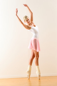 Ballerina standing on tiptoe with raised arms beautiful classical ballet