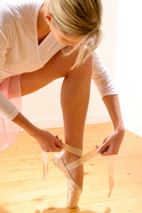 Ballet dancer getting ready for ballet performance woman ballerina tying