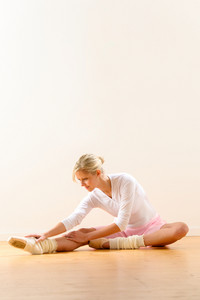 Ballet dancer in leaning posture exercise studio reaching woman ballerina