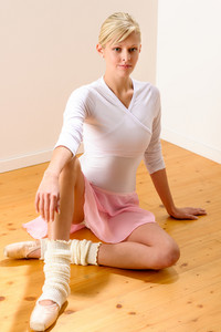 Ballet dancer sitting on the studio floor resting ballerina beautiful