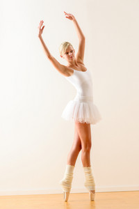 Ballet dancer standing on tiptoe with raised arms